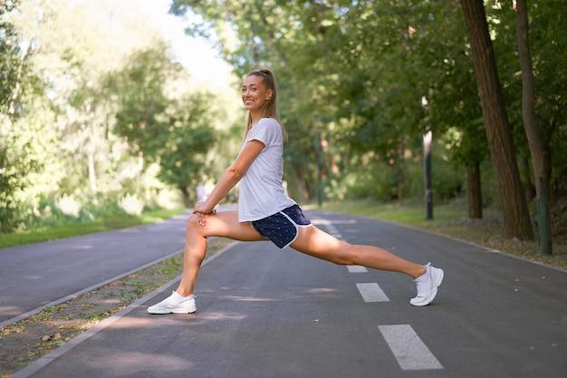 サマーパークの朝を運動する前に足を伸ばす女性ランナー