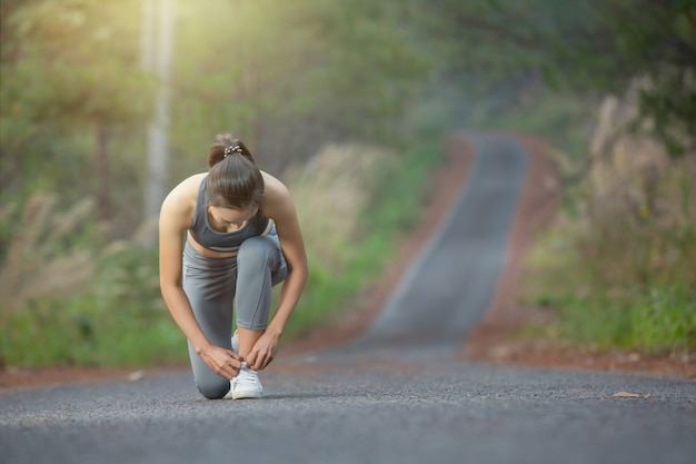 Woman runner tie her shoe during running