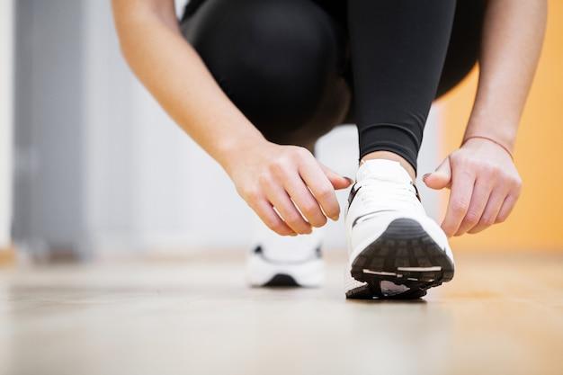 Woman runner tightening shoe lace, runner woman feet running on road closeup on shoe
