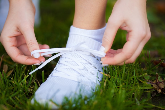 Woman runner tightening shoe lace. runner woman feet running on road closeup on shoe.