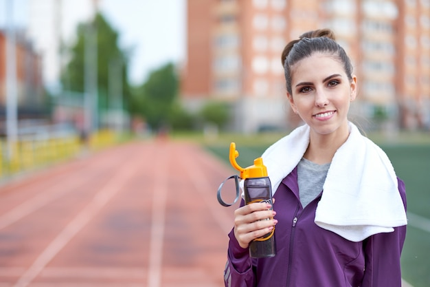 Woman runner with towel resting and drinking water from a bottle after working out track run of stadium