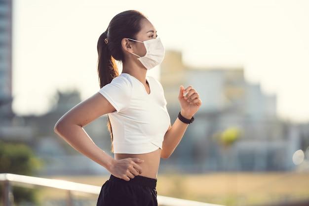 女性ランナーの朝の運動は、鼻マスクを着用しています。ほこりやウイルスに対する保護
