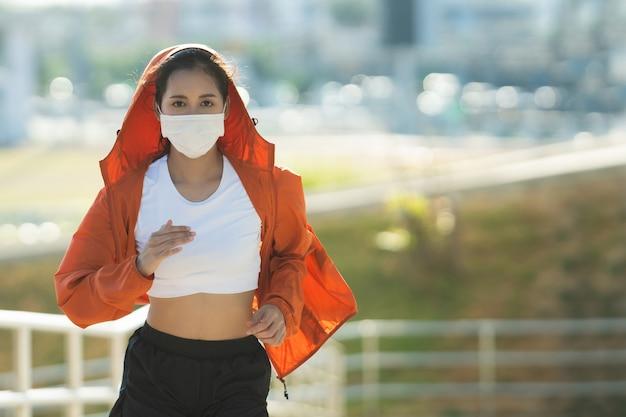 Esercizio mattutino dei corridori della donna che indossa una maschera per il naso. protezione contro polvere e virus