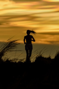 Woman running alone at beautiful sunset. summer sport and freedom concept. athlete training on dusk.