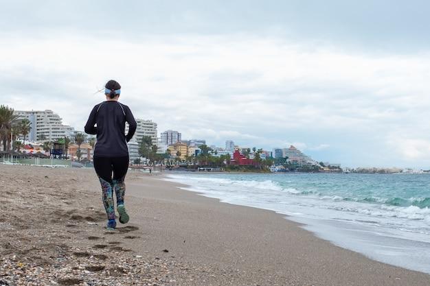 Woman running along the beach on a promenade