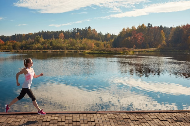 Woman running along a path with lake views, healthy lifestyle