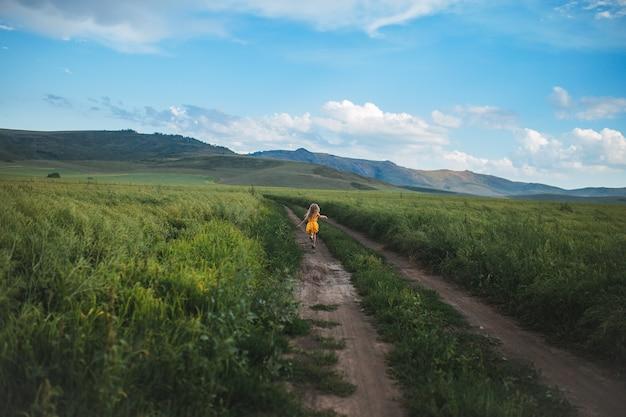 黄色のドレスのフィールドに沿って道路に沿って走っている女性