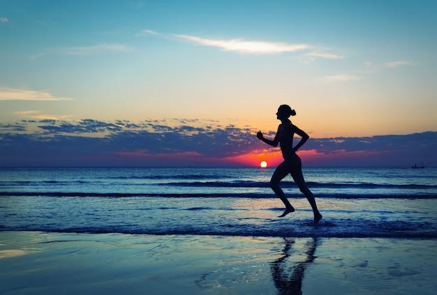 海の海岸に沿って走っている女性