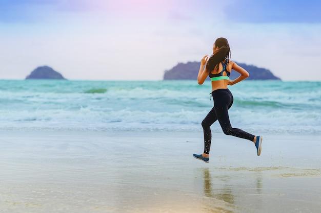 흐린 하늘 해변에서 운동 선수를 실행 하는 여자