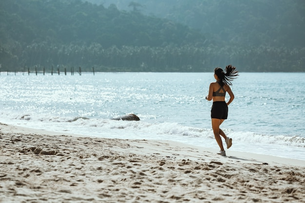 Woman running on the beach in the summer