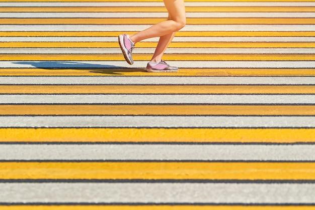 横断歩道を走っている女性、コピースペース。街道でスポーツウェアでジョギングするアスリート女性。健康的なライフスタイル、フィットネススポーツの趣味。交通違反。ストリートワークアウト、屋外での全力疾走