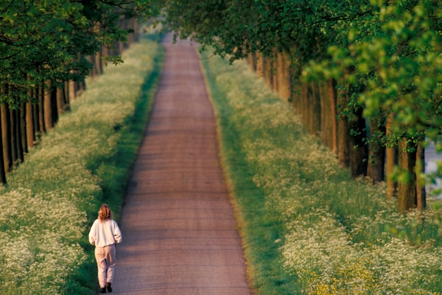 Woman running down remote country lane bordered by wildflowers and trees
