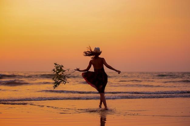Женщина работает в воде на пляже на закате, весело, праздник, отпуск, образ жизни и концепция счастья. сосредоточиться на силуэт
