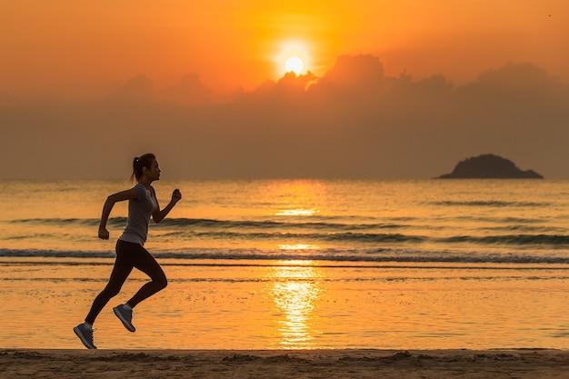 日の出のビーチで水と波を背景に走っている女性。
