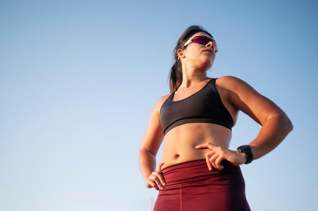 晴れた日の間に市の青い空を背景に道を走っている女性