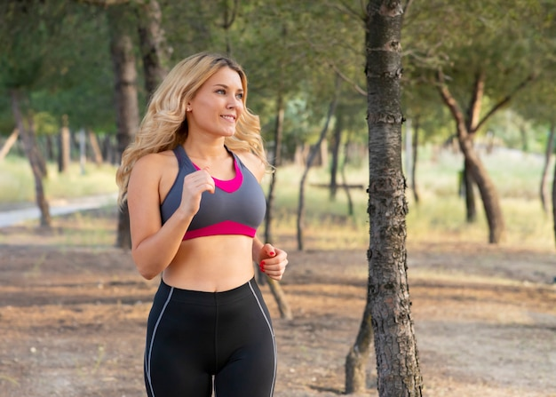 Woman running through the forest happy. outdoor sport concept