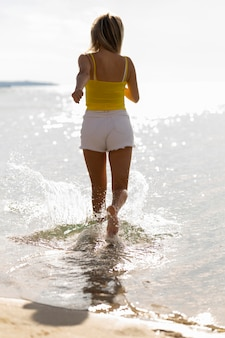 Woman running through water on beach