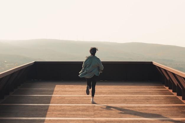 화려한 일몰 자유와 자유 개념 동안 발코니에서 수평선으로 실행하는 여자