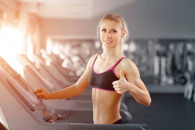 Woman running on a treadmill with a raised thumb