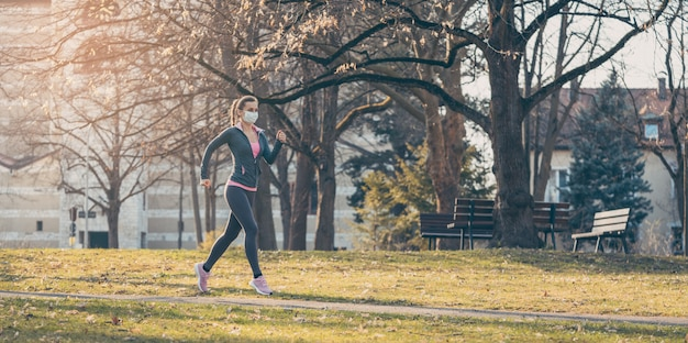 Covid-19中に健康を保つためにフェイスマスクで走っている女性