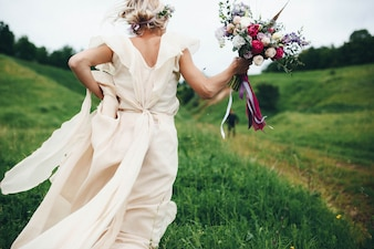 Woman running with the wedding dress and a bouquet