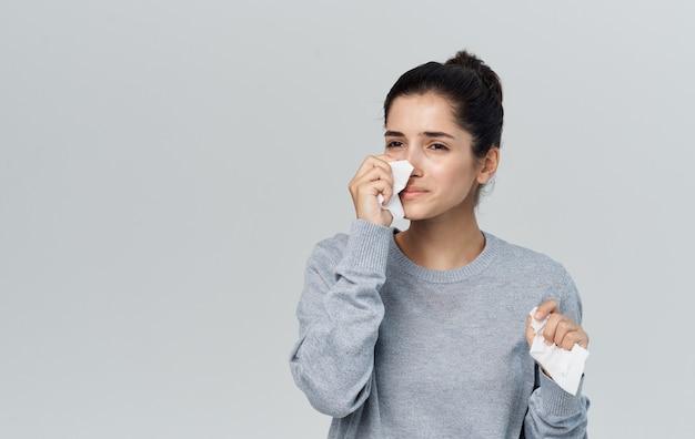 Женщина насморк проблемы со здоровьем серый свитер салфетку. фото высокого качества