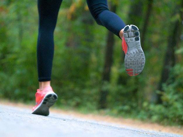 Woman runs in the forest. feet of a runner. close-up of sneakers.