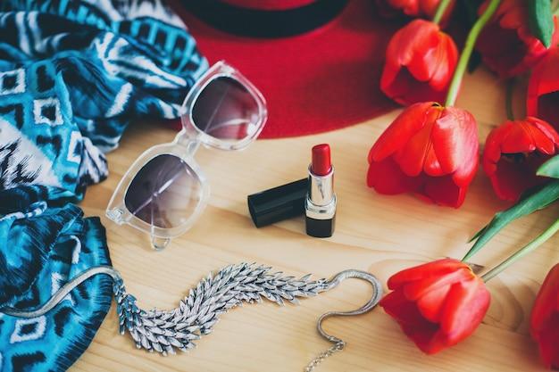 Женские аксессуары и красные тюльпаны на столе