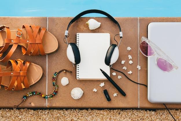 プールの床、静物、上からの眺め、夏のファッショントレンド、休暇、ヘッドフォン、ノートブック、サングラス、サンダル、貝殻、ペン、旅行日記、ブレスレット、花で構成された女性のアクセサリー