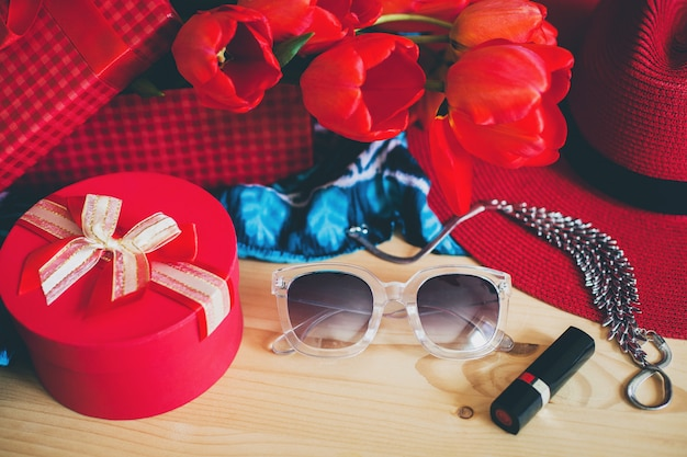 Woman's accessories and red tulips on table