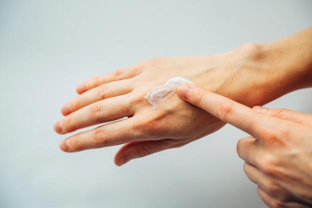 Взрослыми руками женщины нанести питательный крем