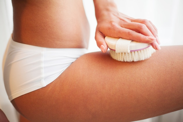 Woman's arm holding dry brush for cellulite treatment