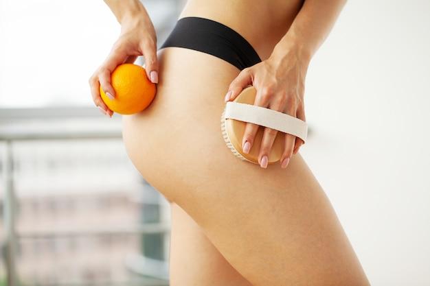 Женская рука держит сухую кисть на верхней части ноги и апельсин, лечение целлюлита и сухая чистка.