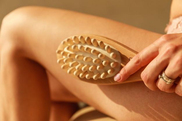 Женская рука держит сухую кисть на верхней части ее ноги. красивая молодая женщина с антицеллюлитной массажной щеткой.