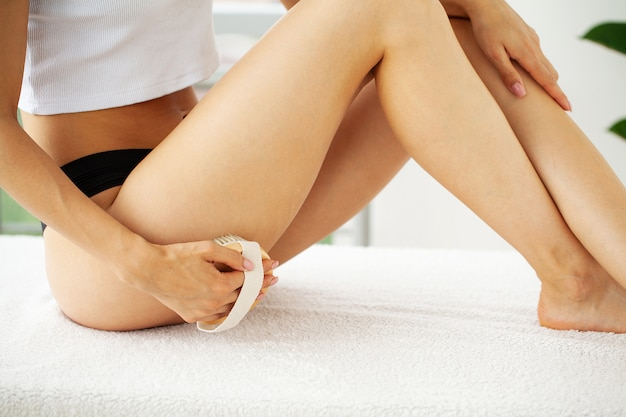 Woman's arm holding dry brush to top of her leg, cellulite treatment and dry brushing.