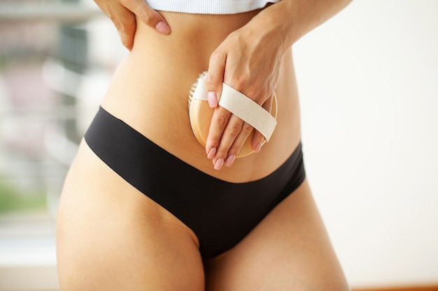 Woman's arm holding dry brush to top of her stomach, cellulite treatment and dry brushing.