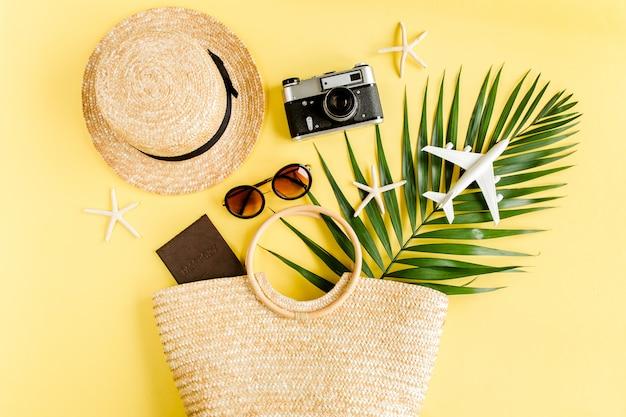 Женские пляжные аксессуары: сумка из ротанга, соломенная шляпа, тропические пальмовые листья на желтом фоне. плоская планировка, вид сверху.