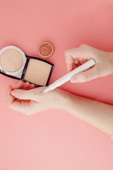 Женский блоггер красоты держит в руках флакон и тюбик профессиональной косметики высокого класса на розовом фоне, концепцию минимализма, теплые уютные тона и copyspace