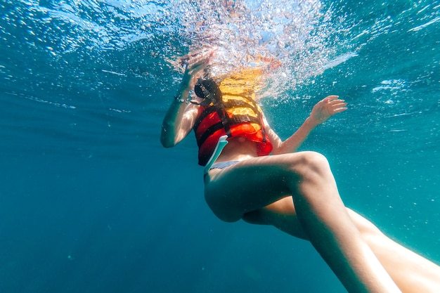 Woman's body in a life jacket floats underwater in the sea on vacation