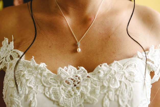 Woman's chest on her wedding day while she dresses.