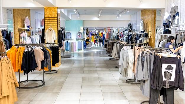 Женская одежда на вешалке в современном магазине-бутике