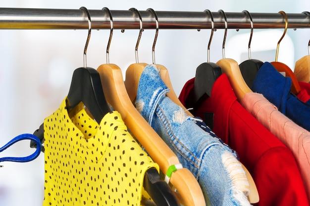 Красочная разная одежда женщины на вешалке крупным планом