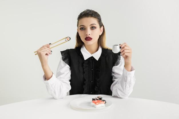 プラスチック製の女性が食べる寿司、エココンセプト。有機的な世界を失う。