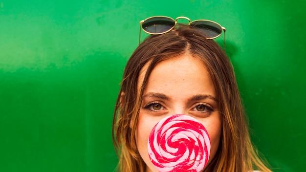 彼女の口の前に赤とピンクのロリポップを持つ女性の顔