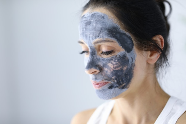 Woman's face is covered with clay cosmetic mask for skin rejuvenation