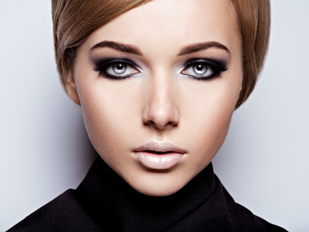 Woman's face with  fashion black makeup of eye and long black eyelashes.
