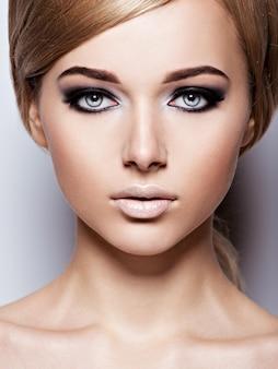 눈과 긴 검은 속눈썹의 패션 블랙 메이크업으로 여자의 얼굴.