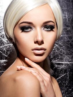 目のファッション黒化粧と長い黒まつげを持つ女性の顔。