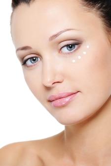 Viso di donna con crema idratante intorno agli occhi