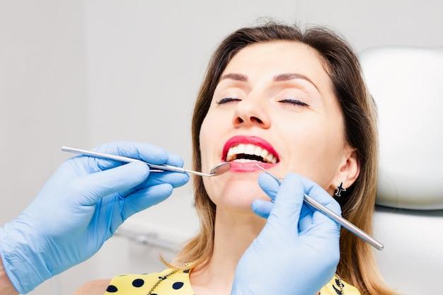医師の診察で口を開けた女性の顔。